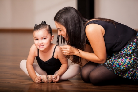 Cute little girl and her dance instructor smiling and having fun during class photo