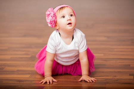 Portrait of a gorgeous little baby girl dressed up as a ballerina and sitting in the dance floor photo