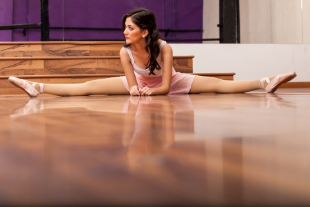 split up: Beautiful ballet dancer stretching and doing a leg split in a dance studio  Lots of copy space on the bottom