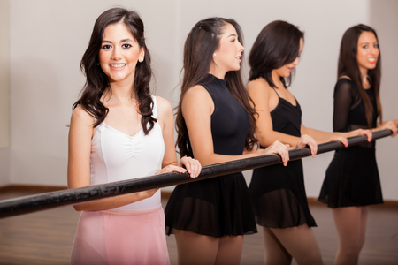 academy: Beautiful ballerinas working out next to a barre in a dance academy Stock Photo