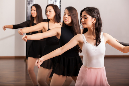 barre: Cute female ballet dancers training in a ballet barre in a dance academy Stock Photo