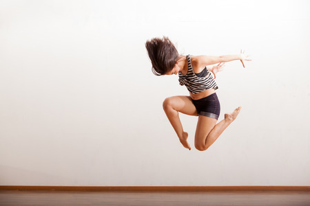 dance floor: Female jazz dancer in the middle of a jump as part of a dance routine