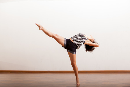 Beautiful jazz dancer performing some sexy dance moves in a studio photo