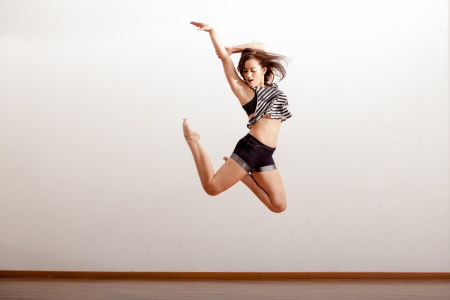moves: Beautiful jazz dancer jumping during a dance rehearsal in a studio