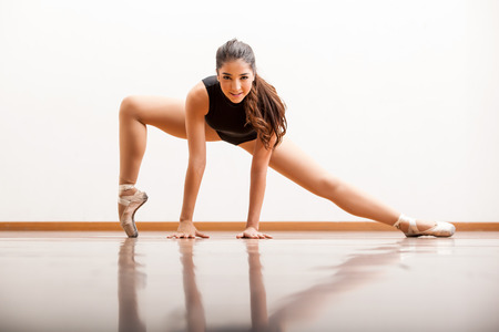 beine spreizen: Wunderschöne Ballettänzerin Üben einige Tanzbewegungen auf der Tanzfläche