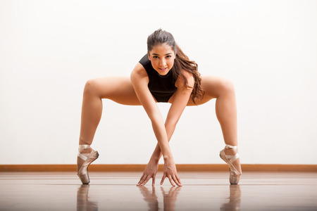 Pretty and strong female ballet dancer holding on a pose during a rehearsal in a dance studio photo