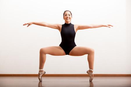 beine spreizen: Schöne Tänzerin mit Spaß und Erhaltung des Gleichgewichts in einem Tanzstudio