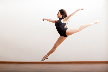 Cute female ballet dancer performing a jump and smiling in a dance studio Фото со стока
