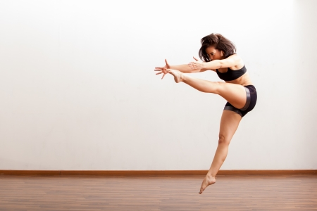 moves: Beautiful Latin jazz dancer performing a dance routine in a dance academy