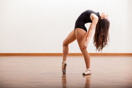 Sexy ballerina rehearsing a dance routine in a dance studio photo