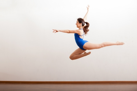 dance studio: Pretty Hispanic ballet dancer practicing a jump as part of a dance routine in a dance academy