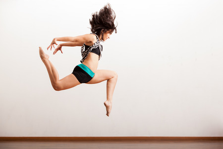 moves: Sexy female jazz dancer in the middle of the air while performing in a studio