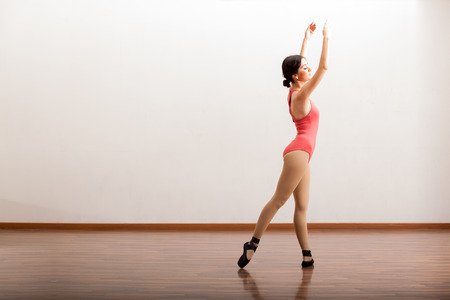 Cute female ballerina holding a ballet pose during a rehearsal in a dance academy photo