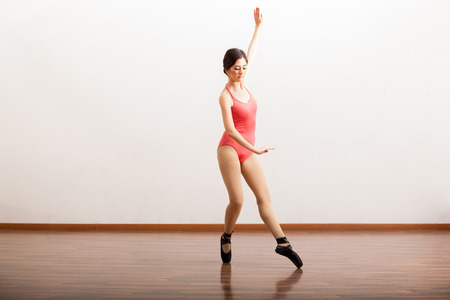 Cute Hispanic ballet dancer performing a dance routine in a dance academy photo