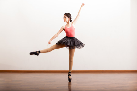 Gorgeous Hispanic ballerina rehearsing a routine in a dance studio photo