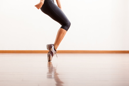 Closeup of a female dancer s tap shoes while she performs in a studio