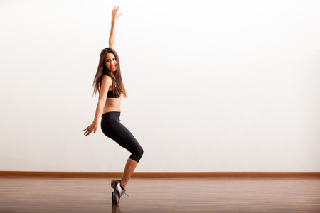 tap dance: Pretty Latin female dancer rehearsing a tap routine in a dance academy