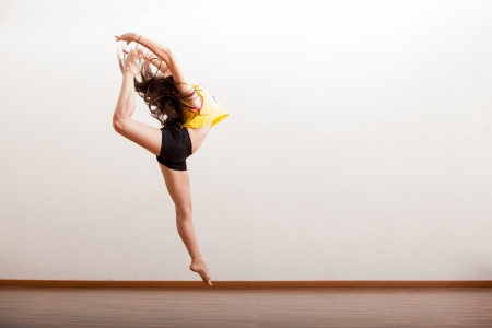 jazz dance: Pretty female jazz dancer caught in the air while performing a dance routine