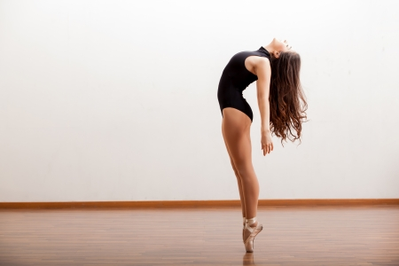 routine: Gorgeous ballet dancer maintaining balance during a dance routine in a studio Stock Photo