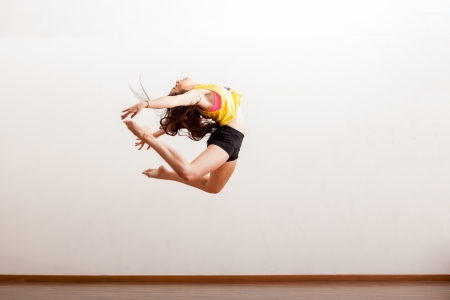 jazz dance: Gorgeous jazz dancer in the middle of a jump during a dance performance in a studio