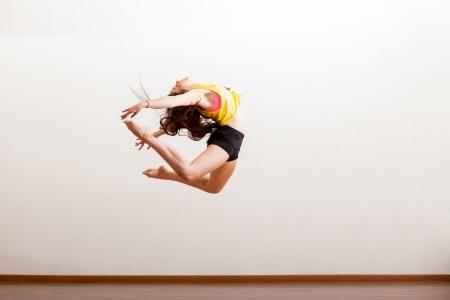 Gorgeous jazz danser in het midden van een sprong tijdens een dansvoorstelling in een studio