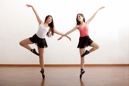 Pretty Hispanic ballet dancers practicing a routine in a dance academy and smiling Zdjęcie Seryjne