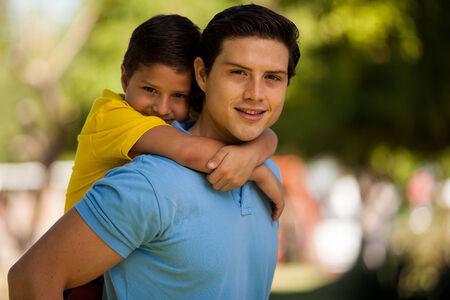 Portret van een jonge Spaanse vader die zijn zoon op zijn rug en glimlachen Stockfoto