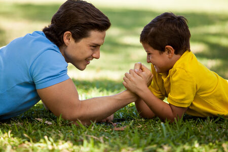 Cute boy trying to beat his dad in arm wrestling while having fun together in a park photo