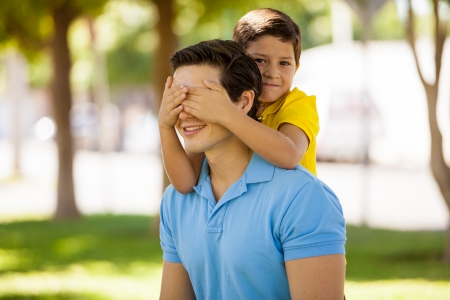 Cute little boy covering his dad s eyes for fun while spending the day outdoors photo