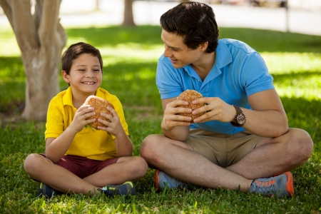 Cute happy boy spending some time with his dad and eating a hamburger in a park photo