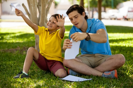 paper folding: Cute Hispanic boy and his dad folding paper planes and having fun outdoors on a sunny day