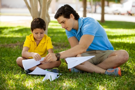 Young father teaching his son how to fold paper planes while spending time together in a park Stock Photo
