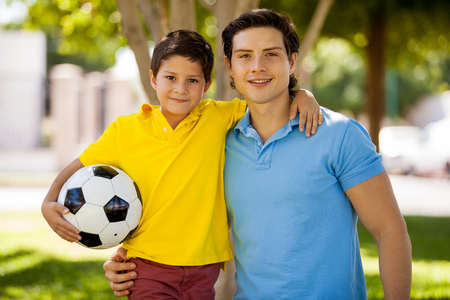 Portrait of a young father and his son about to play soccer at a park and smiling