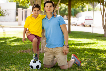 Portrait of a handsome young father and his son with a soccer ball at a park photo