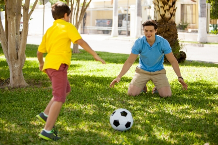 dads: Handsome young father and his son playing soccer and having fun at a park Stock Photo