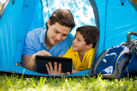 tablet: Cute little boy and his dad using a tablet computer and relaxing on a tent on a camping trip