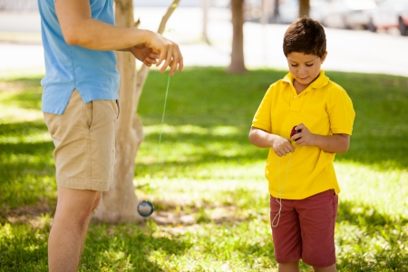 play yoyo: Cute kid learning how to play with a yo-yo with his father