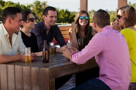 social gathering: Group of young adults hanging out and drinking beer at terrace Stock Photo