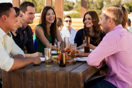 Large group of friends having fun and drinking beer at a restaurant photo