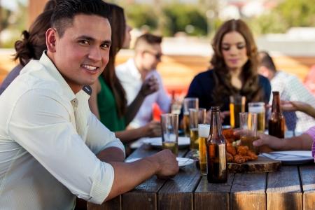 ヒスパニック系の若者の肖像画のバーで軽食と彼の友人のいくつかのビールを持っています。