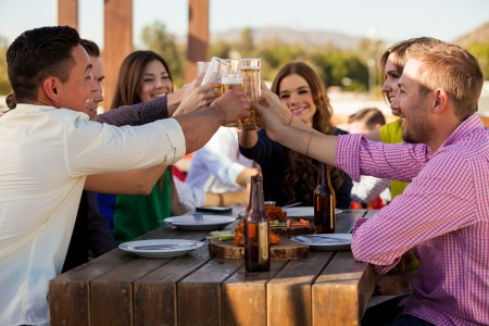 toast: Large group of friends making a toast with beer while hanging out at a restaurant Stock Photo