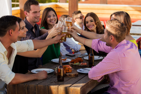 cheers: Large group of friends having fun and drinking beer at a restaurant
