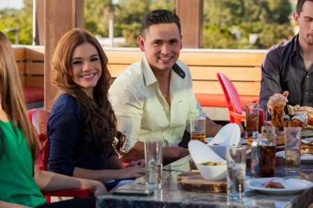 Group of young adults eating out and drinking at a restaurant outdoors Stock Photo - 23562479