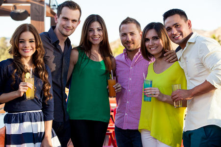 group of young adults: Happy group of young adults having drinks and hanging out at a bar Stock Photo