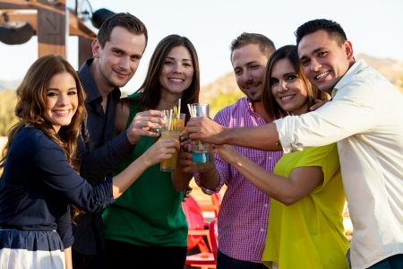 social gathering: Happy group of friends hanging out and making a toast at a bar outdoors