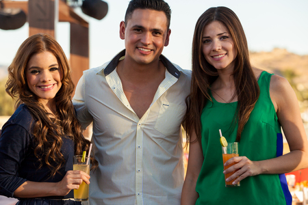 flirting: Portrait of a young handsome man hanging out and having drinks with two female friends