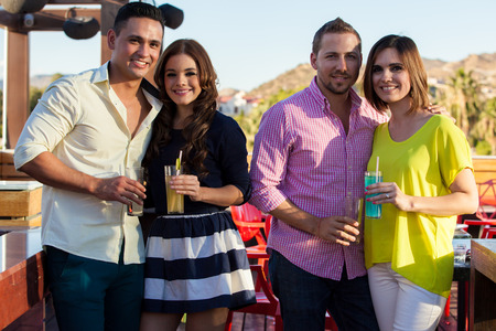 few: Happy young adult couples having a few drinks at an outdoor bar