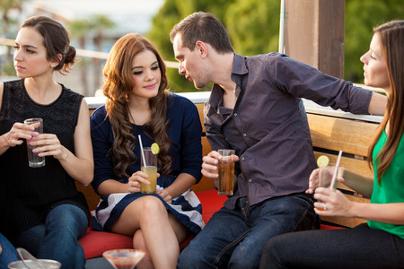 Young Hispanic couple talking and flirting while hanging out with a bunch of friends photo