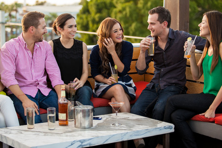 Group of happy young adults having drinks and talking at a terrace photo