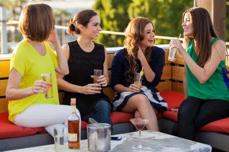 drinking alcohol: Cute female friends drinking alcohol and having fun at a bar Stock Photo
